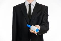 Тема химической чистки и дела: человек в черном костюме держа голубую липкую щетку для очищая одежд и мебель от пыли Стоковое Изображение RF