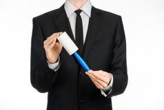 Тема химической чистки и дела: человек в черном костюме держа голубую липкую щетку для очищая одежд и мебель от пыли Стоковая Фотография