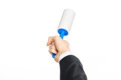 Тема химической чистки и дела: человек в черном костюме держа голубую липкую щетку для очищая одежд и мебель от пыли Стоковые Фотографии RF