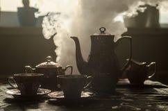 Тема чая и кофе предпосылки еды Старый винтажный керамический бак чая или кофе с чашками кувшином и чашкой сахара на темной предп Стоковые Изображения