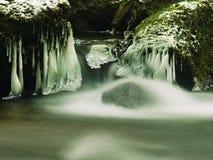 Темная ая-зелен холодная вода потока горы в зимнем времени, малые сосульки висит Стоковое Изображение RF