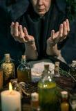 Темная ведьма на работе: женщина черной магии делает witchery путем смешивать травы, бросающ произношения по буквам, бежать волше стоковое фото rf
