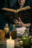 Темная ведьма на работе: женщина черной магии делает witchery путем смешивать травы, бросающ произношения по буквам, бежать волше стоковые изображения rf
