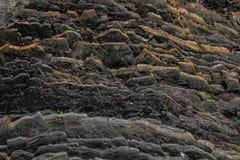 Темная естественная черная вулканическая порода в слоях как абстрактная предпосылка текстуры Стоковое Изображение