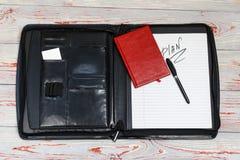 темная кожаная сумка для документов в нем надпись плана слова Ручка, телефон, корона и прачечная там стоковое изображение