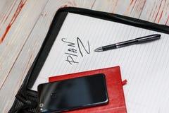 темная кожаная сумка для документов в нем надпись плана слова Ручка, телефон, корона и прачечная там стоковое фото