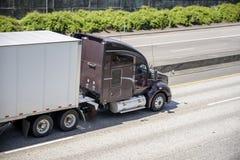 Темная коричневая большого снаряжения коммерчески долгого пути тележка semi транспортируя сухой трейлер фургона semi на дороге ра стоковое изображение