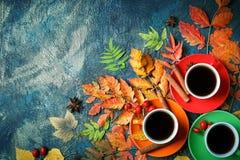 Темная предпосылка осени с 3 чашками кофе и листьями осени Стоковые Фото