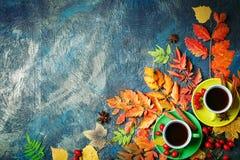 Темная предпосылка осени с чашкой кофе и листьями осени Стоковые Фото