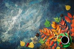 Темная предпосылка осени с чашкой кофе и листьями осени Стоковые Фотографии RF