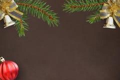 Темная предпосылка с ветвями спруса, колоколов рождества декоративных и красного шарика Стоковые Изображения