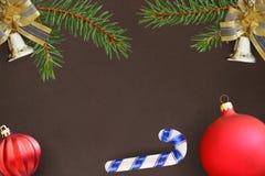 Темная предпосылка с ветвями спруса, колоколов рождества декоративных и красного волнистого шарика, ручки Стоковая Фотография