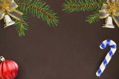 Темная предпосылка с ветвями спруса, колоколов рождества декоративных и красного шарика, ручки Стоковое Изображение RF