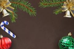 Темная предпосылка с ветвями шарика спруса, колоколов рождества декоративного, красных и зеленых ребристого, ручки Стоковые Изображения RF