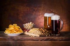 Темное и светлое пиво, закуска солёная и пряная Стоковое Фото
