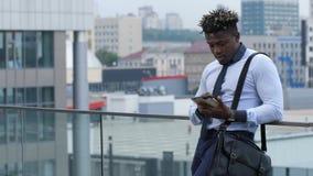 Темнокожий обмен текстовыми сообщениями бизнесмена outdoors видеоматериал