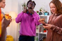 Темнокожий подросток показывая большие пальцы руки вверх после еды пиццы стоковое фото rf