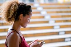 Темнота загорает женщину смешанной гонки кожи для удержания ее мобильного телефона и также для того чтобы стоять путь прогулки по стоковые изображения