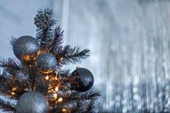 Темнота рождества запачкала предпосылку с черной рождественской елкой, орнаментами и светами bokeh Стоковая Фотография RF