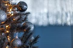 Темнота рождества запачкала предпосылку с черной рождественской елкой, орнаментами и светами bokeh Стоковое Изображение