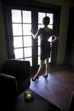 темнота смотря вне детенышей женщины окна комнаты Стоковые Фотографии RF