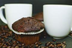 Темные булочки, чашки кофе и кофейные зерна на черной предпосылке Стоковые Изображения RF