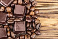 Темные кубы шоколада и зажаренные в духовке кофейные зерна, взгляд сверху Стоковое фото RF