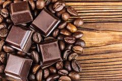 Темные кубы шоколада и зажаренные в духовке кофейные зерна, взгляд сверху Стоковые Изображения