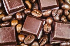 Темные кубы шоколада и зажаренные в духовке кофейные зерна, взгляд сверху Стоковое Изображение