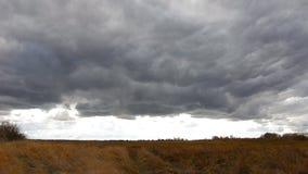 Темные облака шторма летают над полем акции видеоматериалы