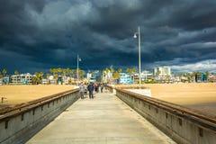 Темные облака шторма над пристанью и пляжем рыбной ловли стоковая фотография rf