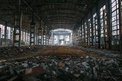 Темные страшные руины сокрушенных покинутых больших промышленных склада или ангара советской фабрики Стоковые Изображения
