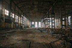 Темные страшные руины сокрушенных покинутых больших промышленных склада или ангара советской фабрики Стоковая Фотография