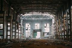 Темные страшные руины сокрушенных покинутых больших промышленных склада или ангара советской фабрики Стоковые Фотографии RF