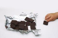 Темные шоколад и рука ребенка Стоковые Изображения RF