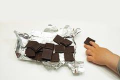 Темные шоколад и рука ребенка Стоковая Фотография