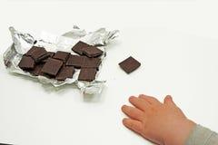 Темные шоколад и рука ребенка Стоковое Изображение RF