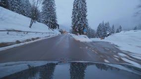Темный автомобиль двигает на дорогу в районе пригорода среди снега покрыл деревья и холмы сток-видео