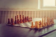 Темный деревянный набор шахмат перед игрой на доске стоковое фото