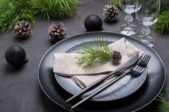 Темный дизайн сервировки стола рождества Черные плиты, стекла шампанского, вилка и набор ножа с салфеткой, ветвью ели стоковое фото