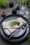 Темный дизайн сервировки стола рождества Черные плиты, стекла шампанского, вилка и набор ножа с салфеткой, ветвью ели стоковое фото rf