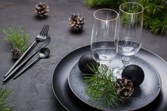 Темный дизайн сервировки стола рождества Черные плиты, стекла шампанского, вилка и набор ножа с салфеткой, ветвью ели стоковые фото