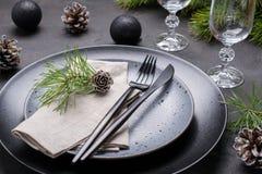 Темный дизайн сервировки стола рождества Черные плиты, стекла шампанского, вилка и набор ножа с салфеткой, ветвью ели стоковые изображения