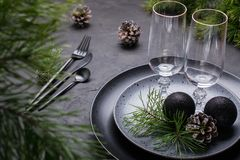Темный дизайн сервировки стола рождества Черные плиты, стекла шампанского, вилка и набор ножа с салфеткой, ветвью ели стоковые фотографии rf