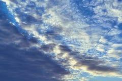 Темный кумулюс и светлые пернатые облака на голубом небе Стоковая Фотография