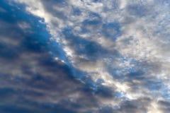 Темный кумулюс и светлые пернатые облака на голубом небе Стоковые Фото