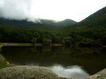 Темный лес осени вокруг горы облаков около озера Стоковая Фотография