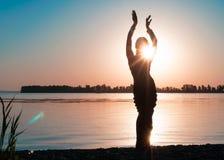 Темный силуэт танцевать тонкая женщина около большого реки стоковое фото rf