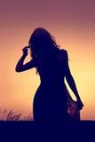 Темный силуэт молодой женщины с длинными волосами идя в l Стоковое Фото