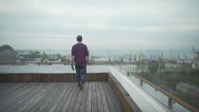 Темный с волосами человек в вскользь одеждах с журналом в руке идя на деревянную крышу смотря seascape гавани на пасмурный день акции видеоматериалы